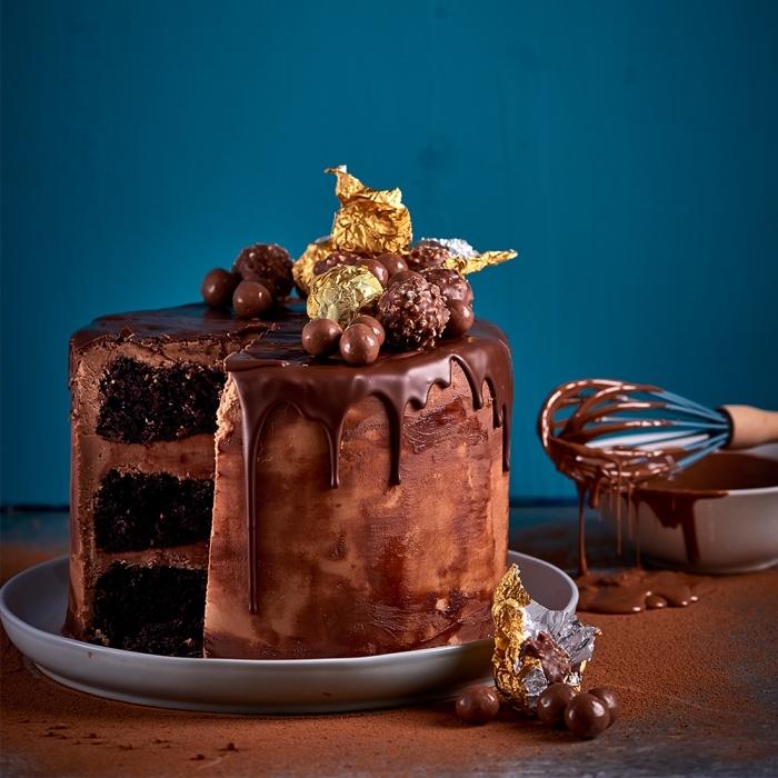 idée de gateau au chocolat anniversaire décadent composé de trois génoises au chocolat recouvertes de crème beurre au nutella, au glaçage coulant de chocolat