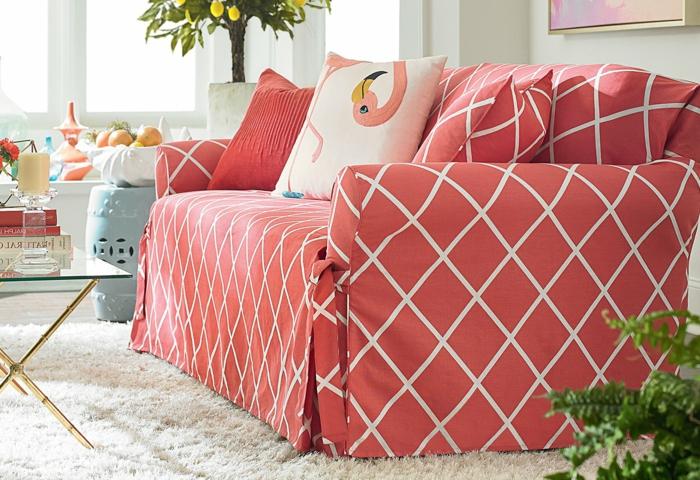 sofa tapissé, tapis blanc, table basse en verre et métal doré, coussins flamingue, arbres décoratifs