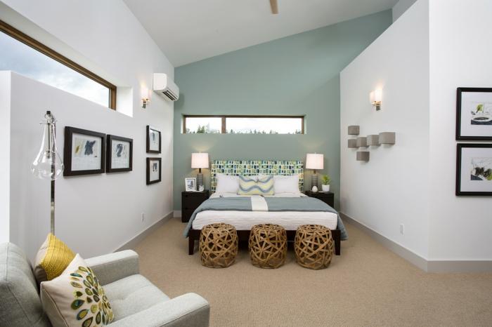 trois tabourets en matière naturelle, fauteuil gris clair, tableaux encadrés, mur bleu, appliques murales
