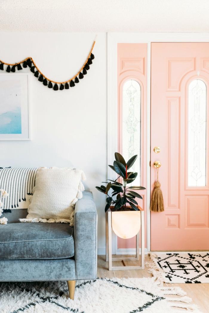 grande porte couleur corail, table de chevet pliante, plante décorative, guirlande de franges suspendue au mur, sofa bleu