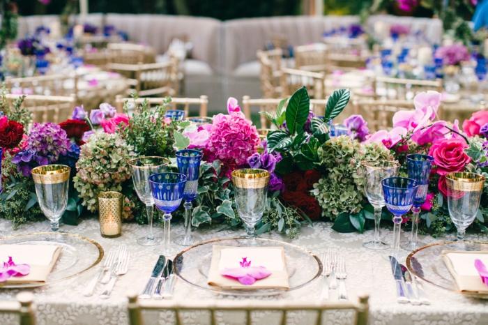 déco florale au centre de la table de mariage, verres aux rebords dorés et aux dessins bleus, assiettes transparentes, nappe blanche