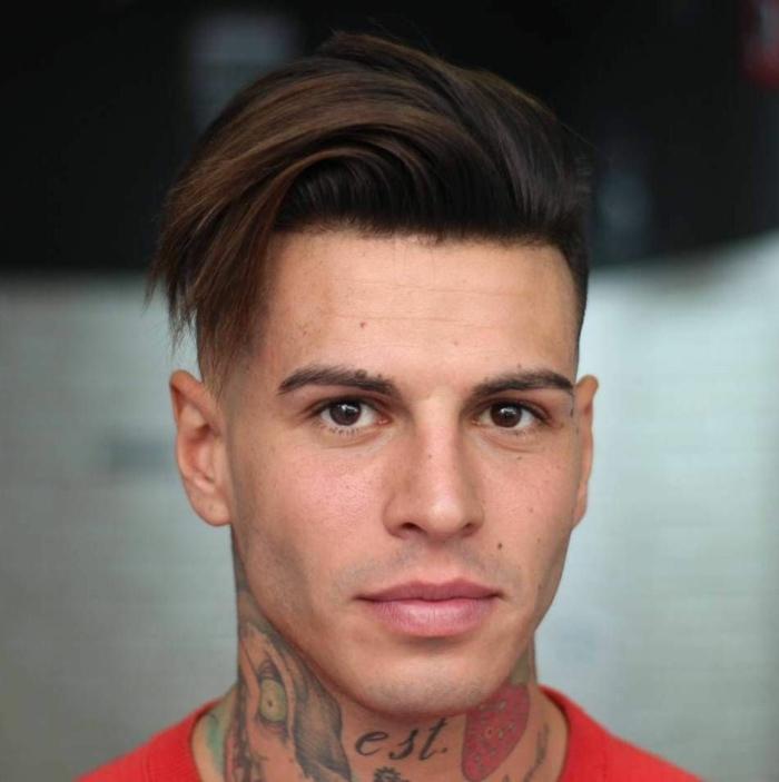 frange sur le coté au-dessus du front, cheveux longs au sommet, rasés des côtés, tatouages au cou