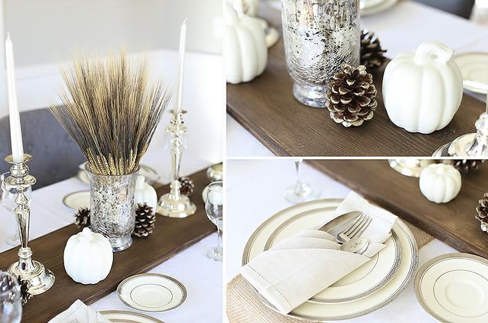 planche de bois peinte, assiettes aux rebords argentés, pommes de pin, vase avec brins de fleurs sèches, citrouilles peintes