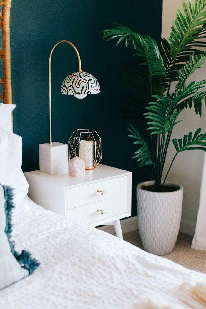 déco de chambre en bleu et blanc, lampe de chevet bras doré, petit chevet blanc, grand pot de fleur blanc; peinture murale bleue