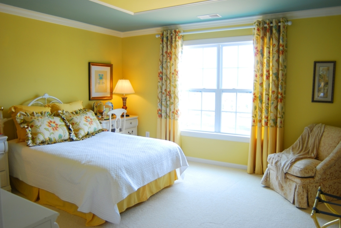 chambre en jaune et bleu, coussins déco aux volants, plafond bleu et jaune, sol blanc, grand fauteuil draperie vintage