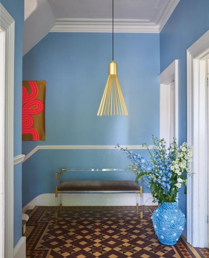 idée déco couloir aux murs peints en couleur bleu clair lumineux mise en valeur par quelques accents dorés et par le carrelage céramique en tons terre