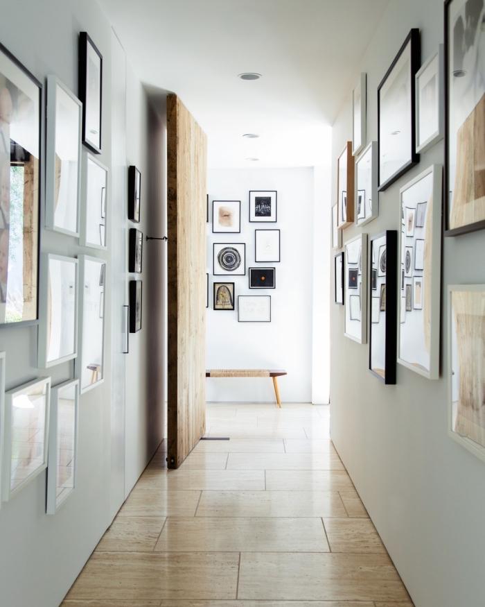 murs de cadres aux formats variés qui introduisent des touches de noir dans ce couloir blanc monochrome