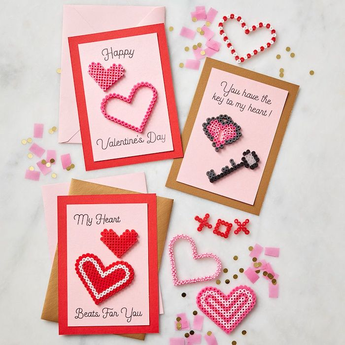 perles à repasser modele rangées en forme de coeur et clé et collées sur papier rose et rouge, idée surprise saint valentin