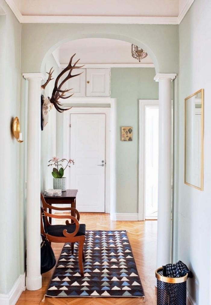 les murs vert menthe à l'eau très clair s'associe à merveille avec le parquet en bois bons et la boiserie peinte en blanc pour créer une ambiance chaleureuse dans le couloir, quelle couleur peindre un couloir avec beaucoup de portes