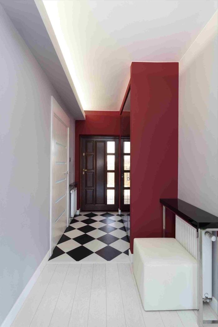 couloir rouge, blanc et gris clair au sol vinyle imitation damier noir et blanc