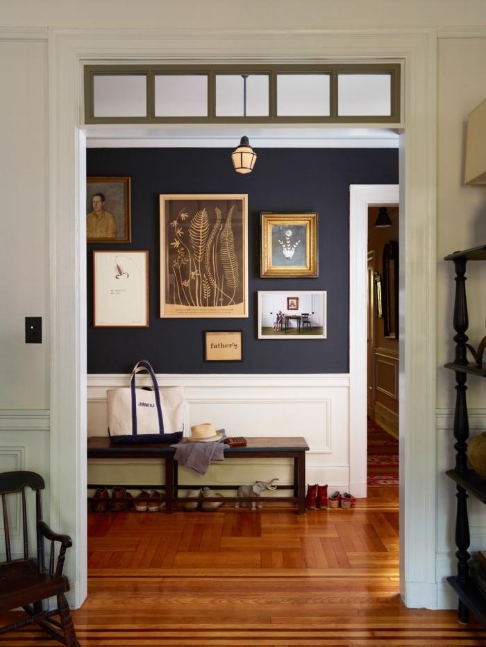 idée peinture couloir associant un teinte bleu nuit sur la partie haute de la mur et un soubassement peint en blanc pour un joli effet de contraste, déco de couloir telle une galerie avec des cadres vintage sur le fond bleu