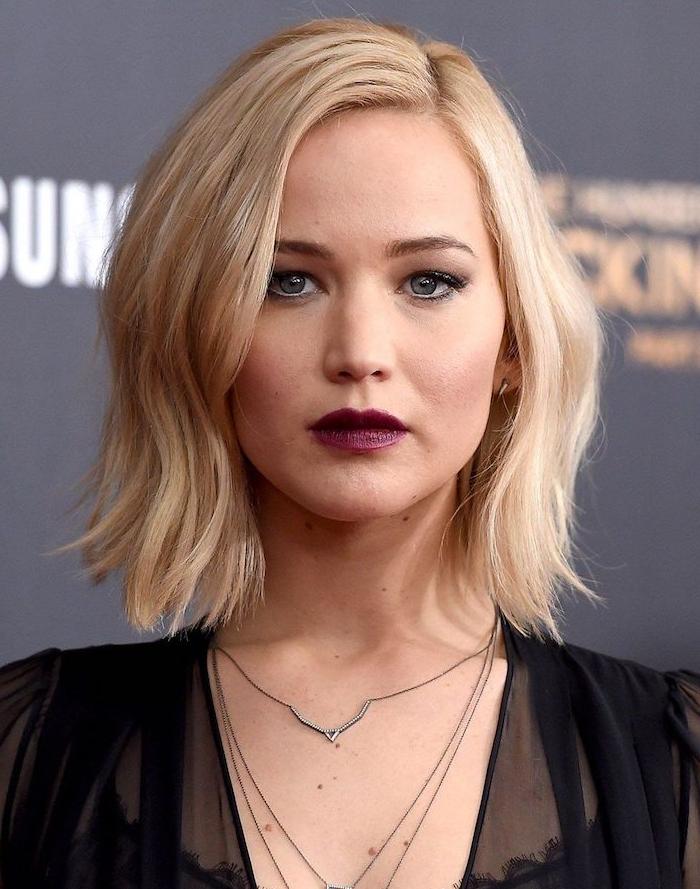coupe carré dégradé sur cheveux blond aux bouts ondulés, raie sur le coté et robe longue noire, rouge à lèvres bordeaux