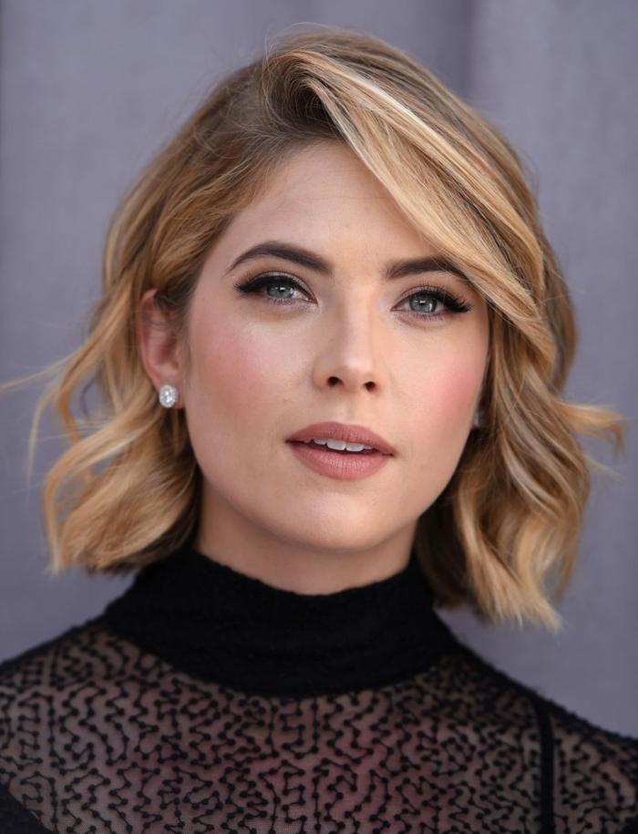 coiffure wavy, cheveux blonds, col montant, tenue noire avec dentelle, frange de côté