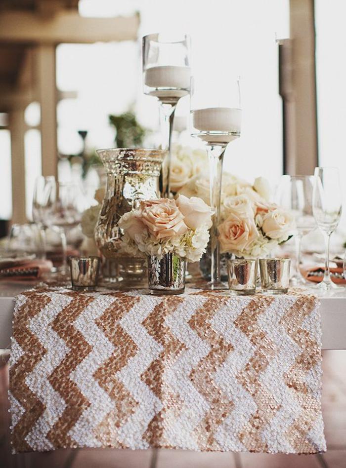 chemin de table blanc aux motifs graphiques dorés, verres remplis de roses crème, porte-bougies hauts