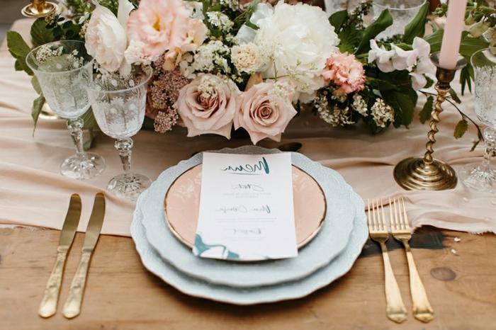 chemin de table rose, deux assiettes blanches et une cuivrée, centre de table mariage roses et feuillage