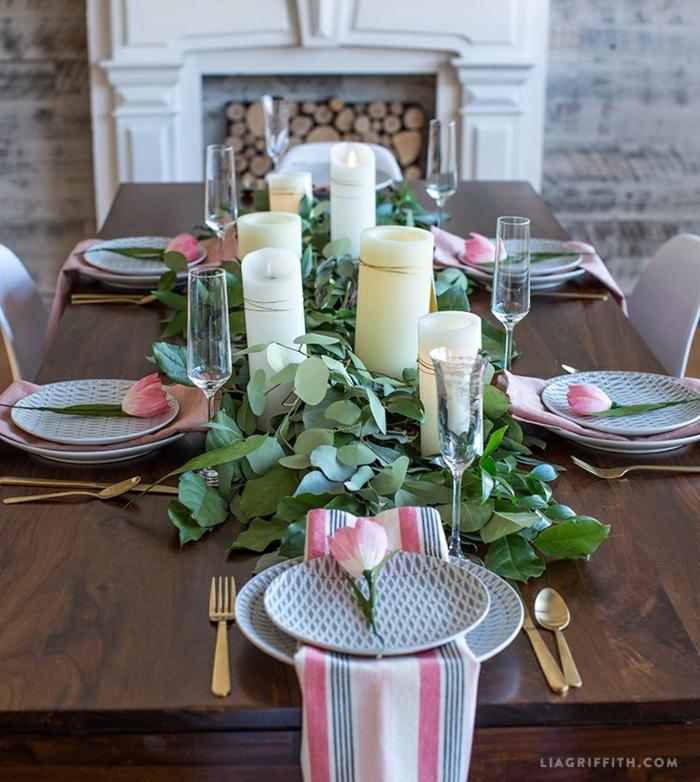 assiettes aux motifs graphiques, bougies blanches, verres à champagne longues, cheminée et bûches