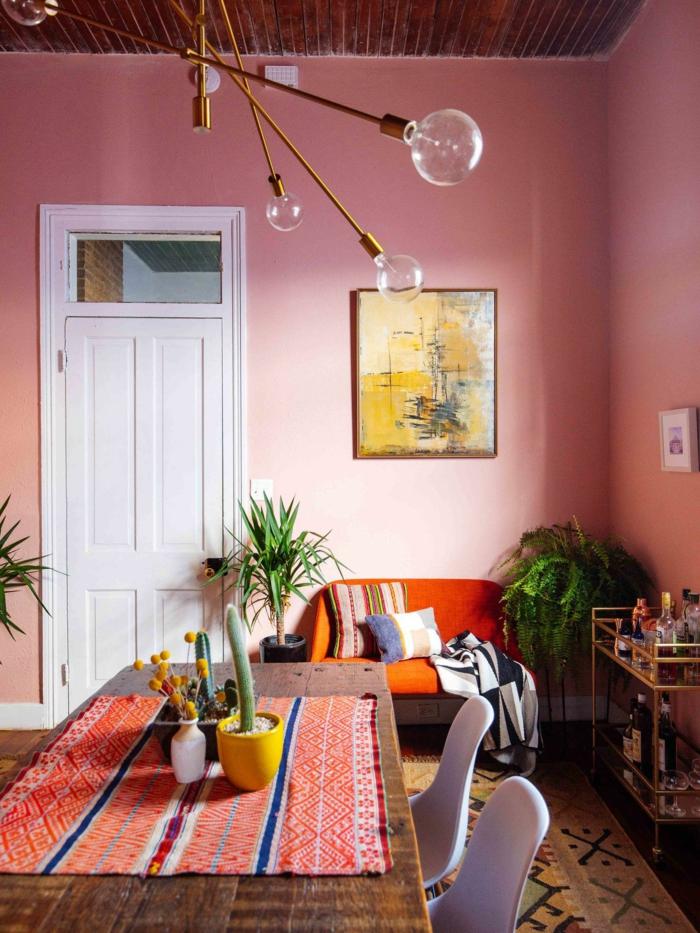 peinture murale couleur saumon, table en bois, nappe de table ethnique, tableau mural jaune, lampe molécule, plante verte, deux chaises blanches