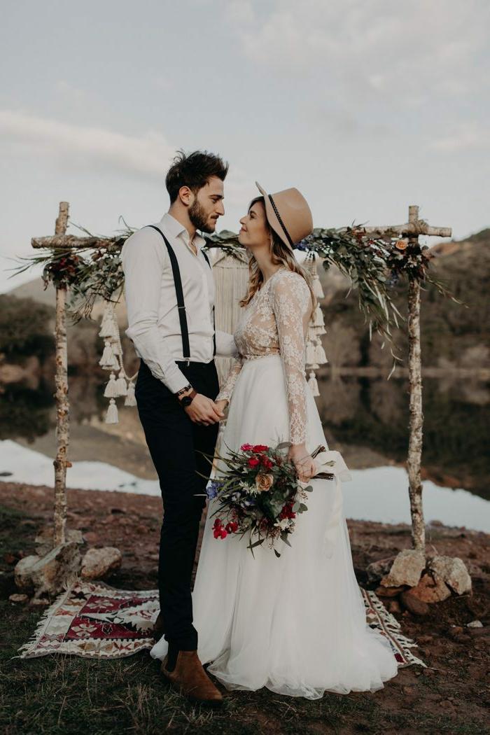 chaussures montantes, pantalon noir, bretelles, chemise blanche, mariée avec chapeau feutre et bouquet de fleurs rouges