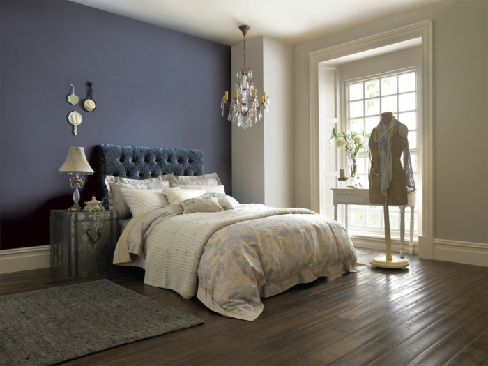 chambre féminine, tête de lit gris anthracite, sol en bois, chandelier en cristal, porte-manteau mannequin, tapis gris