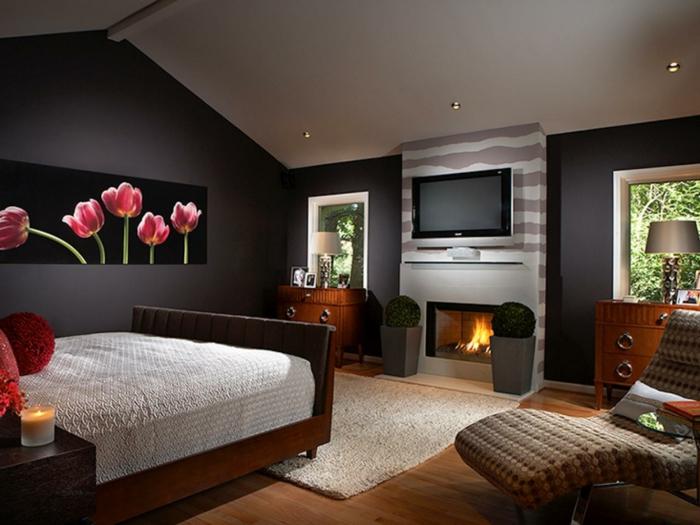tableau tulipes au mur, cheminée, grand fauteuil tressé, lit en bois, couleur mur chambre noir et blanc