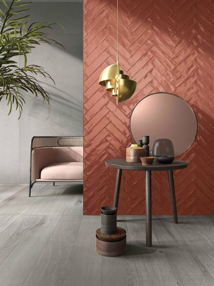 cloison en couleur tendance, miroir rond, lampe suspendue dorée, sofa rose saumon, mur gris clair