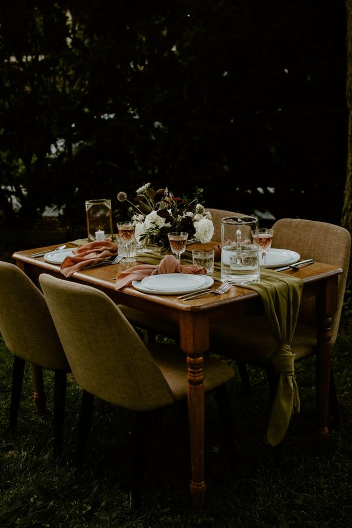 table de bois avec un chemin de table vert en tissu, assiettes blanches, serviettes de table roses, bouquet de fleurs blanches