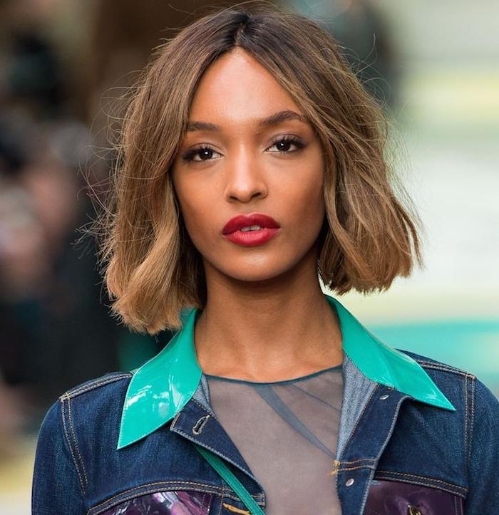 coupe carré mi long sur cheveux chatain clair, style décoiffé de tous les jours, raie ai milieu, rouge à lèvres rouge, veste en jean
