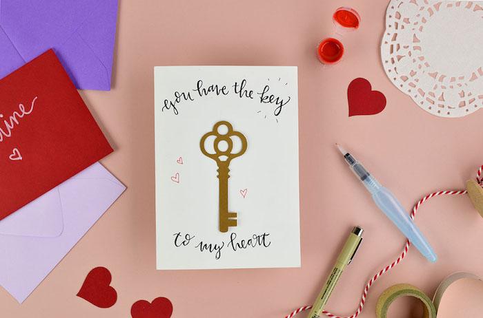 clé carton couleur or collé sur papier blanc avec écriture en lettres noires calligraphie dessus, petits coeurs sur papier