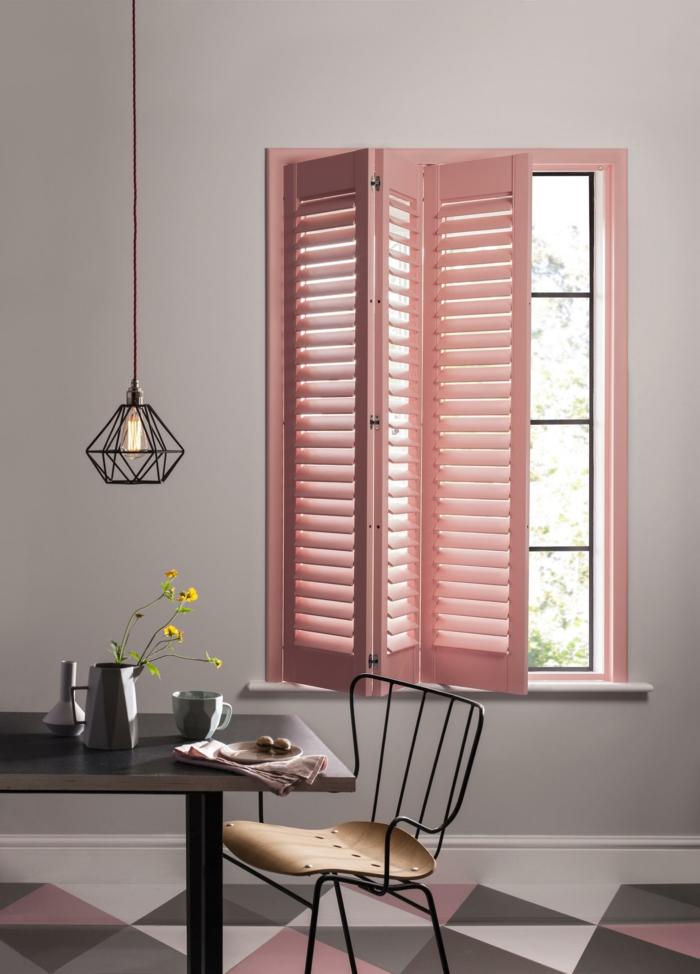 fenêtre peinte en couleur pêche, lampe suspendue industrielle, table en bois, chaise métallique, peinture murale grise