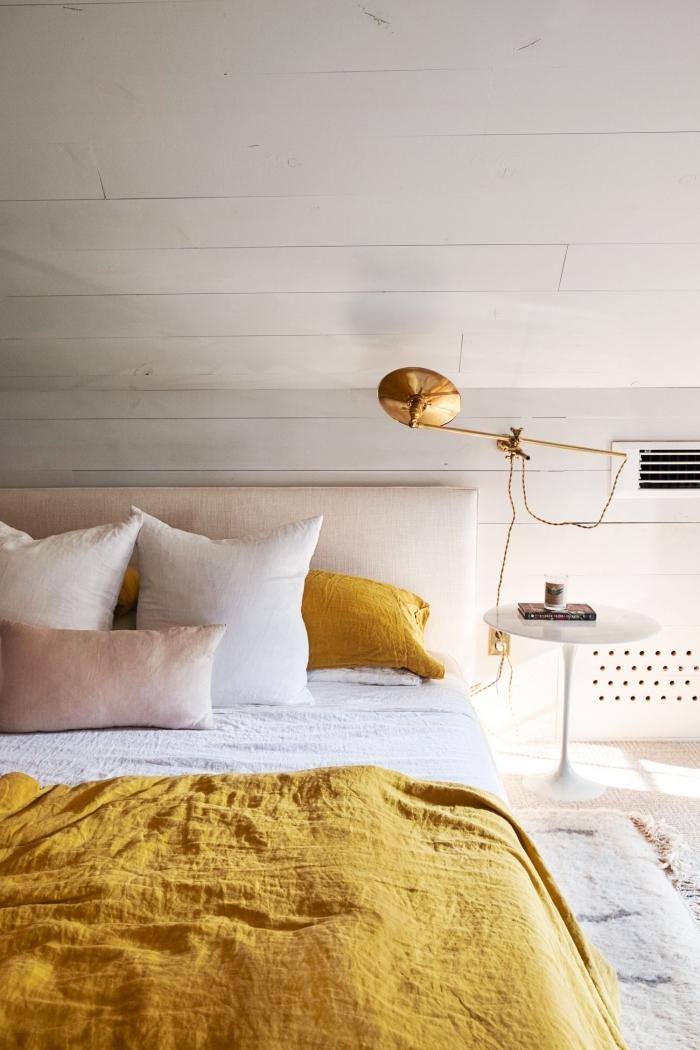 exemple chambre à coucher blanche sous pente, modèle grand lit avec tête de lit beige et couverture de couleur moutarde