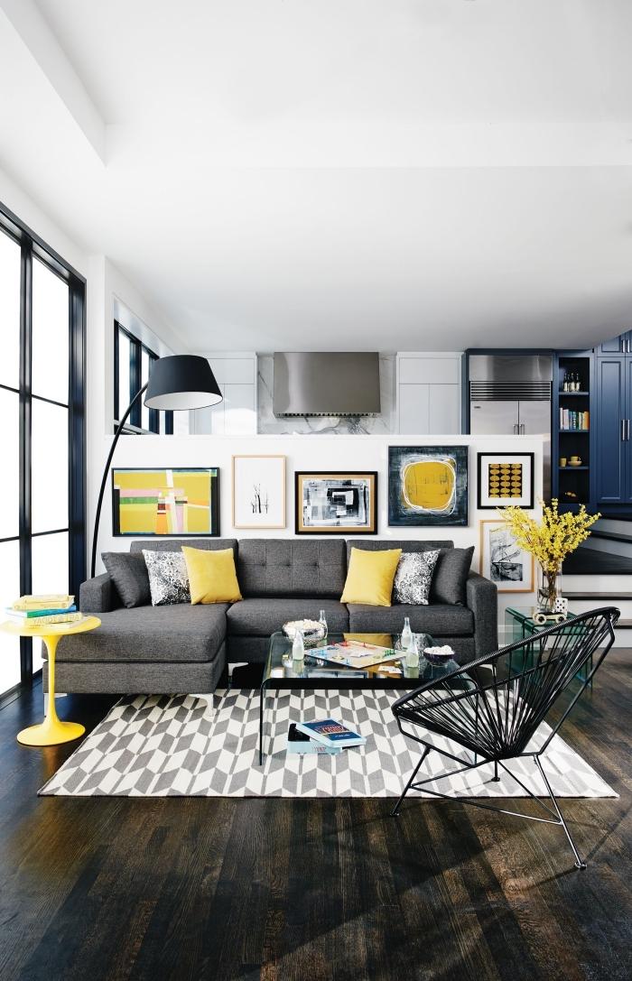 idée déco de salon gris et jaune, pièce blanche avec meubles foncés et accents jaune, mur de cadres dans le salon