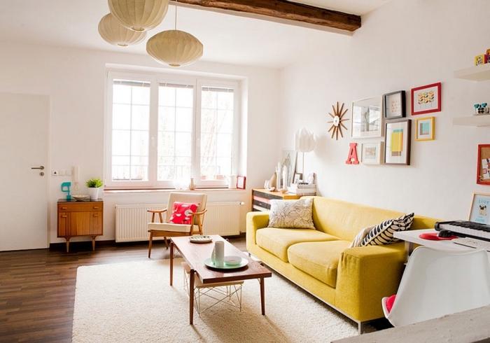 déco cozy dans un salon blanc avec parquet foncé, modèle de tapis moelleux blanc, modèle canapé jaune avec coussins