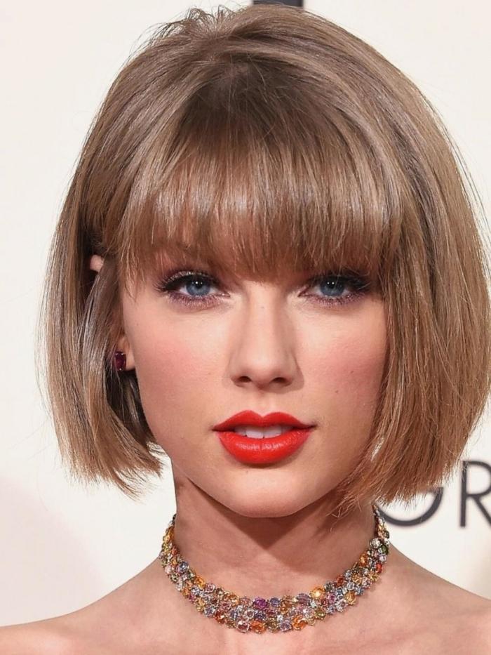 carré plongeant asymétrique de Taylor Swift, lèvres rouges, eyeliner noir, frange droite, cheveux couleur blond cendré