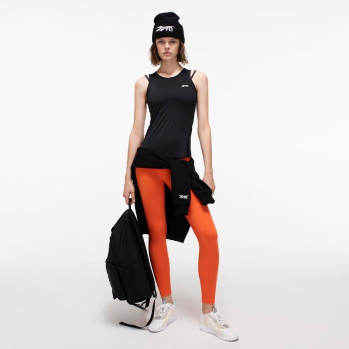 idée bonnet sportif en noir, top noir pour femme, modèle legging en orange, sac à main unisexe noir de la collection Reebok et Victoria Bechkam