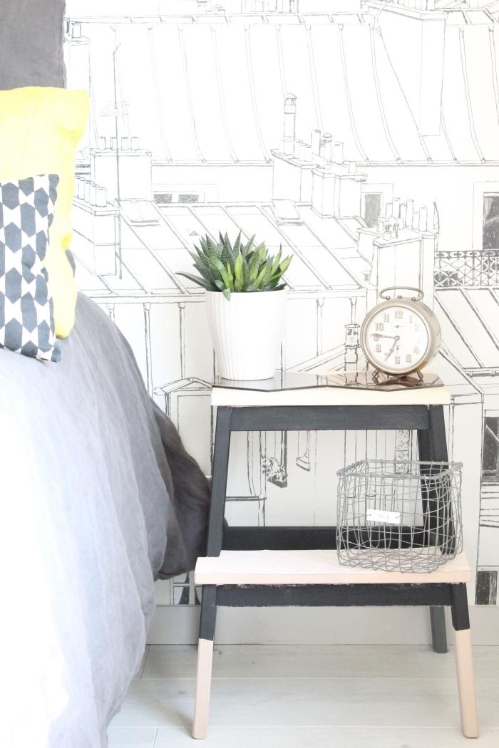 marchepied bekväm en bois et gris qui sert de table de table de chevet scandinave et s'harmonise avec le papier peint graphique derrière le lit, ikea bidouille pour détourner un meuble de son usage principal