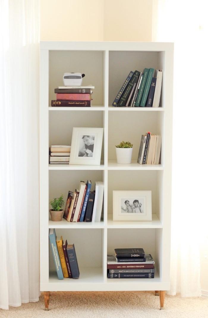 une étagère kallax avec pieds en bois rajoutés qui sert de bibliothèque, idée pour relooker un meuble à petit prix
