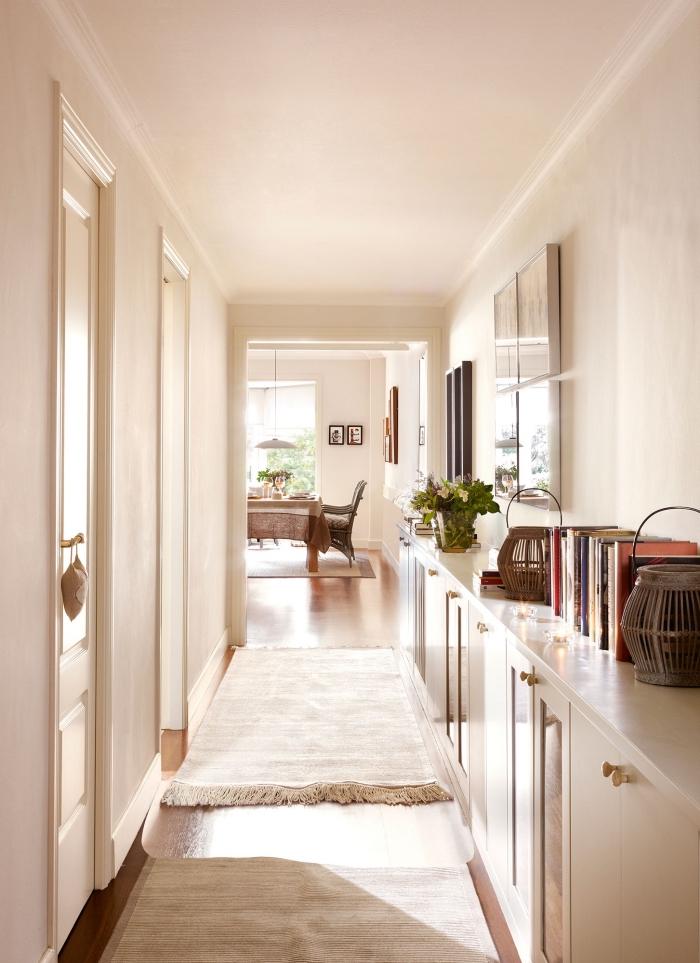 couloir lumineux qui se fond dans l'intérieur clair de l'appartement, meuble entrée couloir sur toute la longueur du mur de la même couleur blanc cassé que les murs