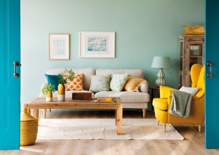 idée deco jaune moutarde avec accessoires ou meubles modernes, salon aux murs vert pastel avec parquet bois clair et accents en couleurs