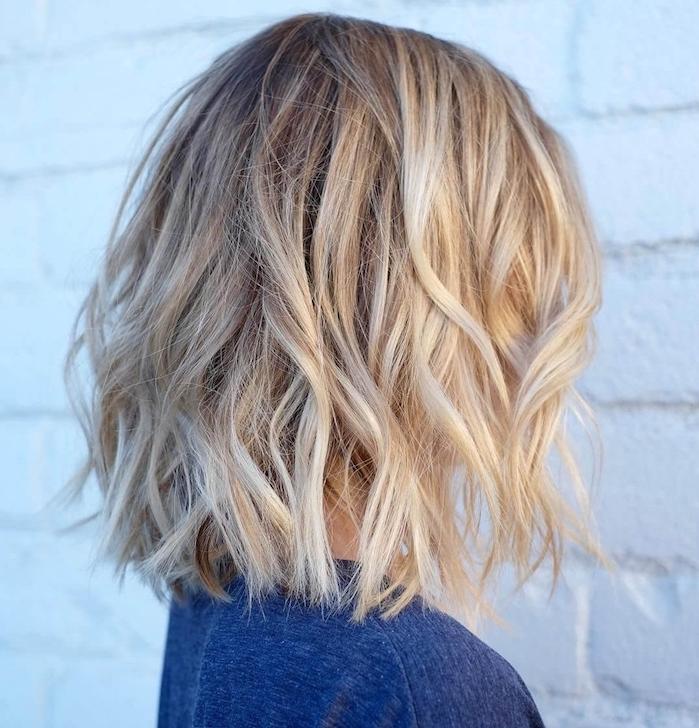 cheveux blond coupés en carré avec effet coiffé décoiffé et voume sur les cotés, blouse couleur bleue