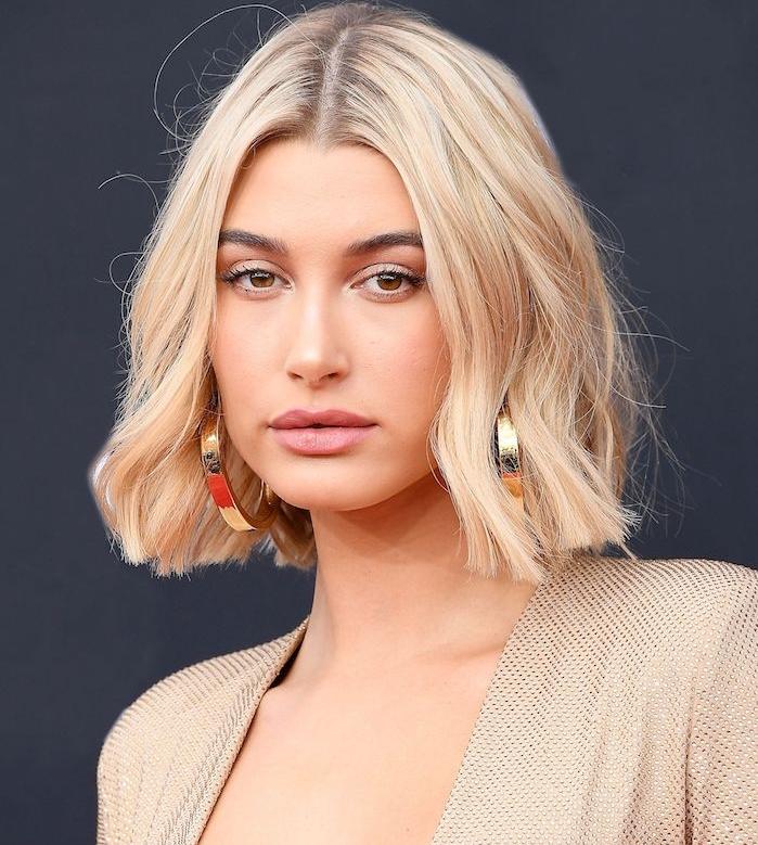 maquillage nude en combinaison avec une coiffure carré ondulé blond et raie au milieu, boucles d oreille or
