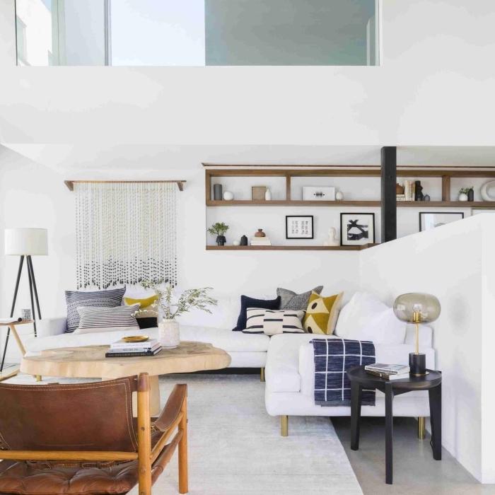 déco minimaliste aux murs blancs et meubles de bois, modèle de grand canapé d'angle décoré avec coussins