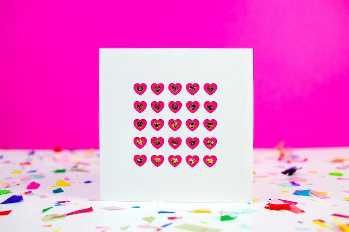plusieurs petits coeurs rose foncé décorés de strass rangés sur papier blanc en lignes et colonnes, idée carte de voeux originale