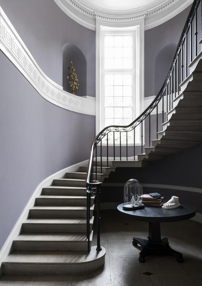 une cage d'escalier spacieuse et élégantes aux murs en violet avec des niches murales de la même couleur et une frise blanche qui traverse le mur