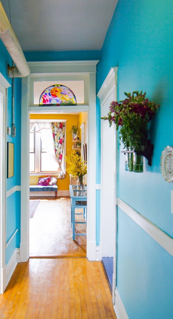 déco couloir étroit aux murs peints en couleur bleu turquoise lumineuse, qui donne sur un salon jaune curry