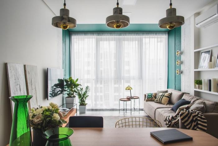 déco de salon avec pan de mur en couleur vert d'eau, modèle de canapé beige décoré avec coussins de couleurs neutres