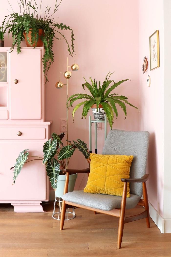 design intérieur féminin dans un salon aux murs rose pastel et parquet bois, modèle chaise fauteuil bois foncé décoré de coussin couleur moutarde