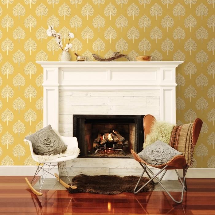 salon cozy avec cheminée blanche, modèle de papier peint de couleur moutarde avec dessins arbres, tapis faux fur marron imitation peau animale
