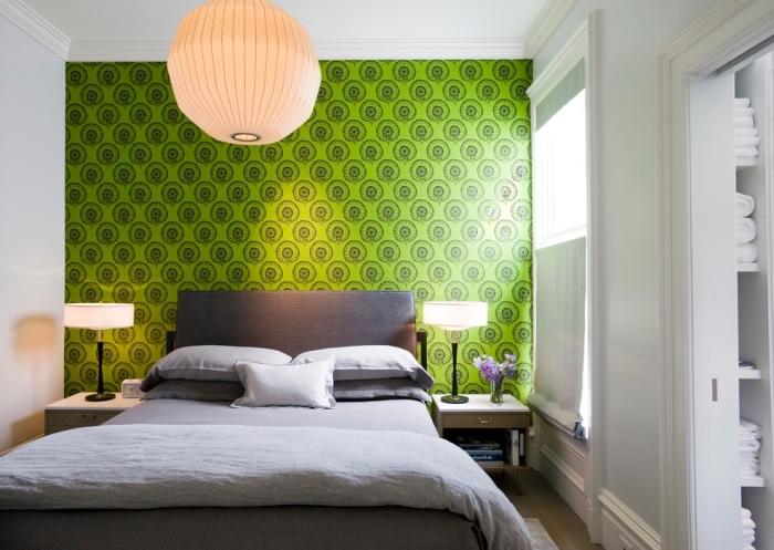 design petite chambre aux murs blancs avec pan de mur en papier peint de couleur vert anis, modèle grand lit gris anthracite