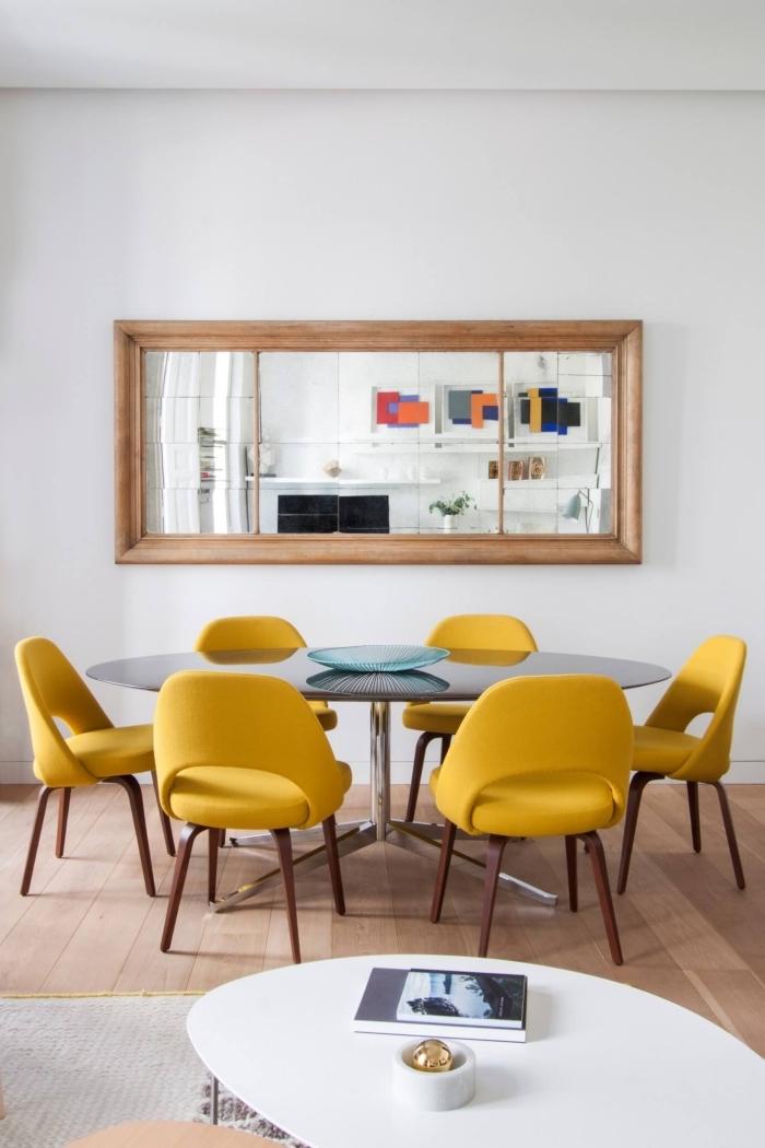 déco salle à manger aux murs blancs avec plancher de bois, modèle de table à manger en verre et métal ronde