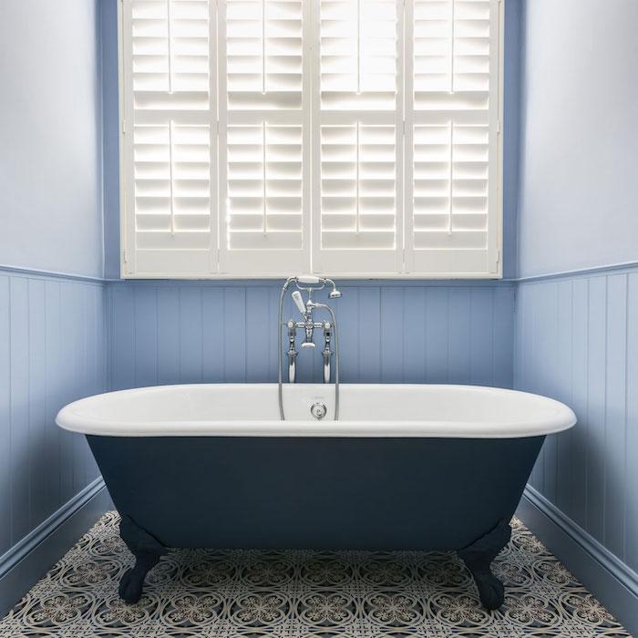photo de baignoire ilot rétro sur pieds après rénovation de peinture bleu marine sur carrelage et murs bleu lavande